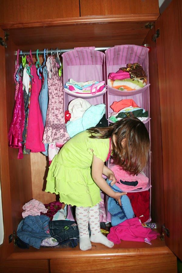 Criança que escolhe o vestido em seu wardrobe fotografia de stock royalty free