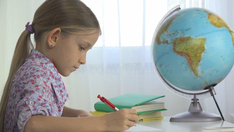 Criança que estuda o globo da terra, menina que escreve para a escola no escritório, aprendendo a criança foto de stock royalty free
