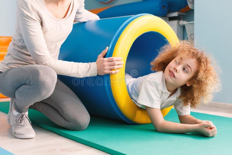 Criança que exercita com túnel do jogo foto de stock royalty free