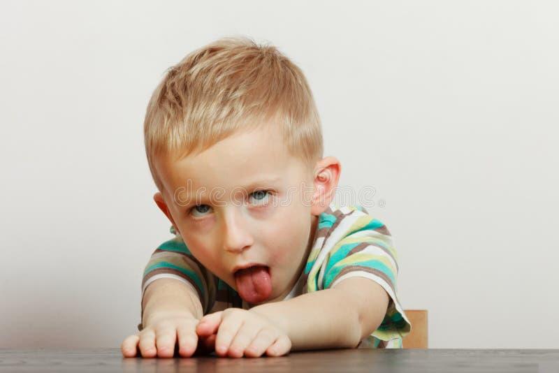 Criança que faz as caras engraçadas que estão sendo furadas fotos de stock royalty free
