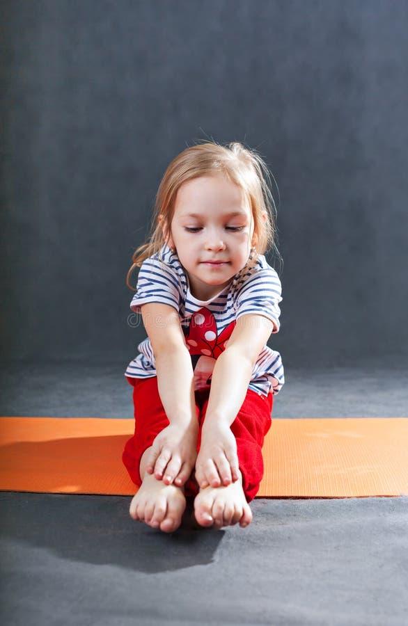 Criança que faz exercícios da ioga da aptidão foto de stock