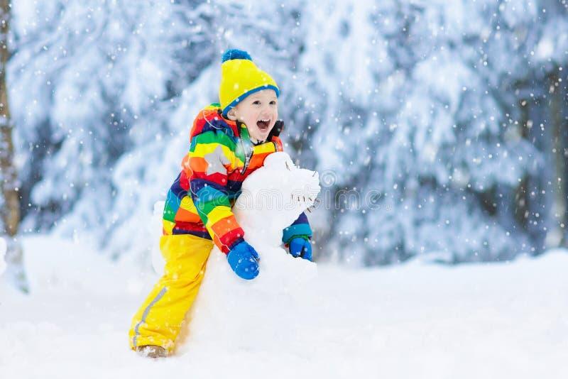 Criança que faz o boneco de neve Jogo das crianças na neve no inverno foto de stock royalty free
