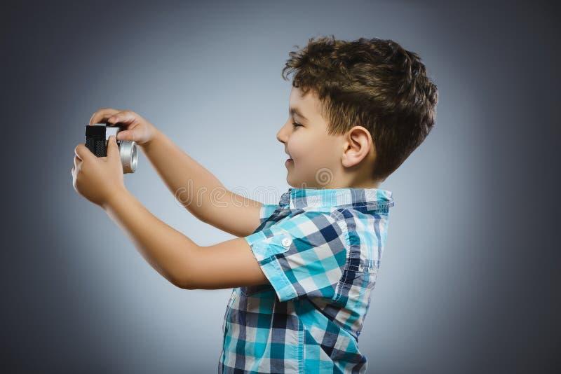 A criança que faz o selfie que usa uma câmera retro do rangefinder isolou o fundo cinzento fotos de stock royalty free