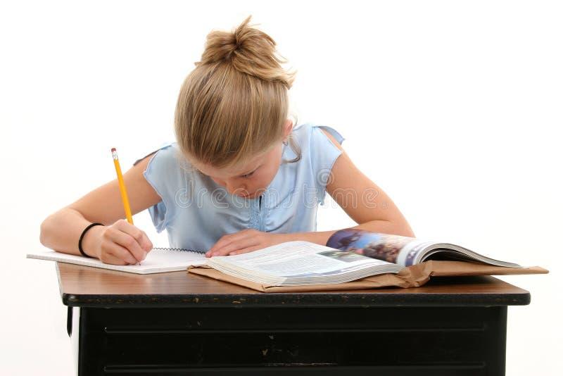 Criança que faz o trabalho da escola na mesa foto de stock royalty free