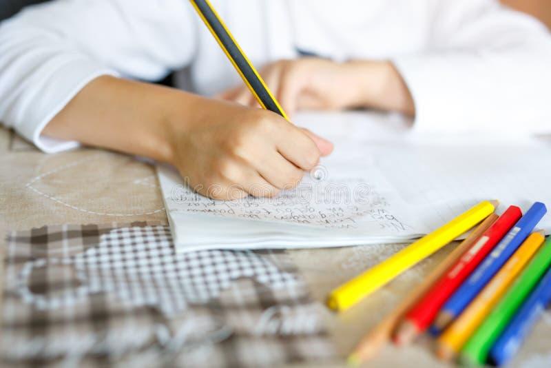 Criança que faz trabalhos de casa e que escreve o ensaio da história Classe elementar ou de escola primária Close up das mãos e d foto de stock