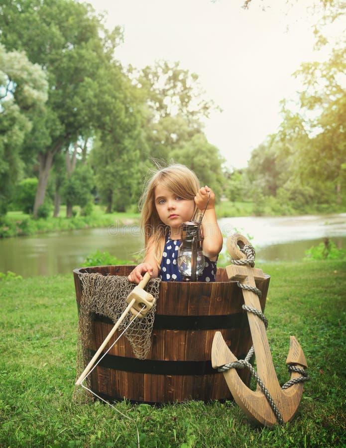 Criança que finge pescar no barco de madeira pela água fotografia de stock royalty free