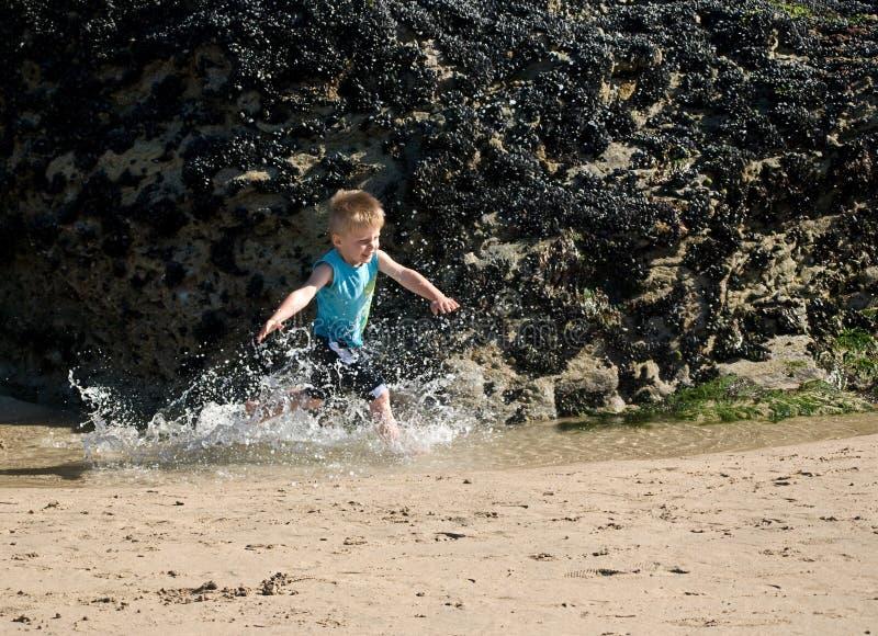Criança que funciona através da água. imagem de stock royalty free