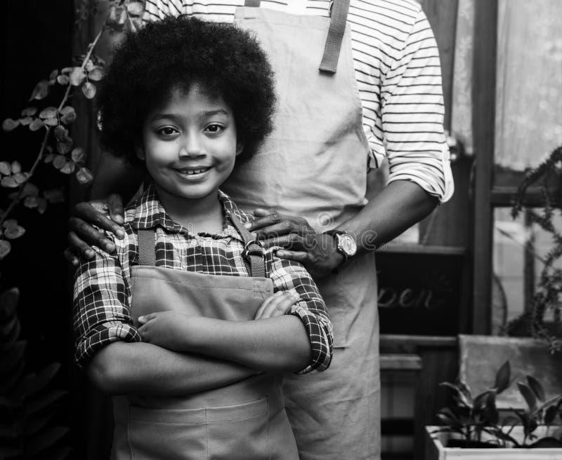 Criança que gesticula o suporte na frente da loja das plantas fotos de stock