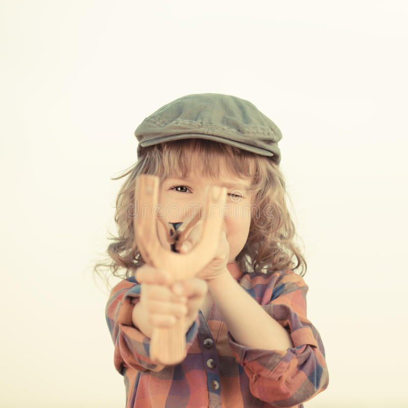 Criança que guarda o estilingue nas mãos foto de stock royalty free