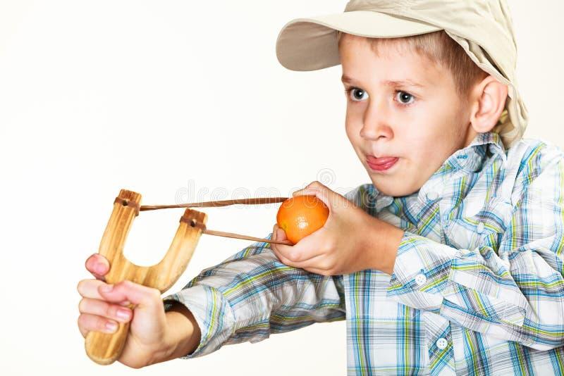 Criança que guarda o estilingue nas mãos imagens de stock