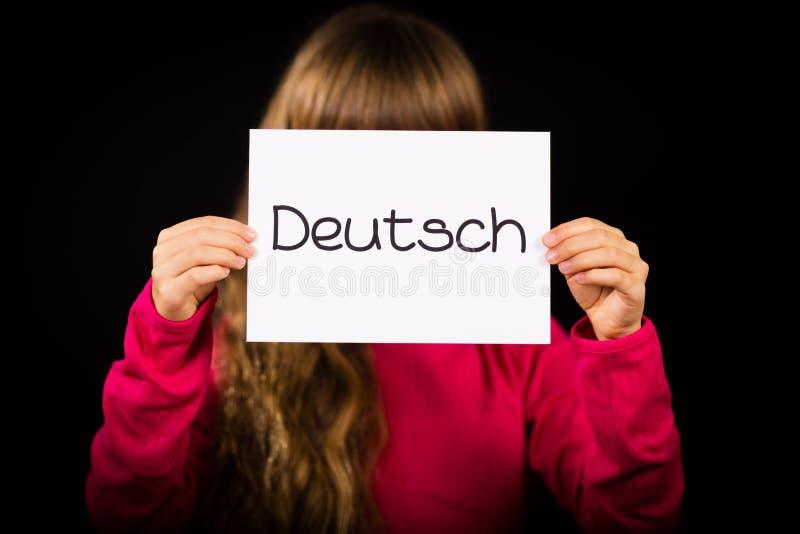 Criança que guarda o sinal com palavra alemão Deutsch - alemão em inglês fotos de stock royalty free