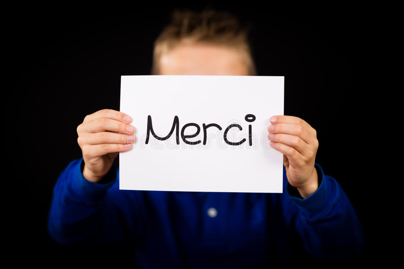 Criança que guarda o sinal com palavra francesa Merci - obrigado imagens de stock royalty free