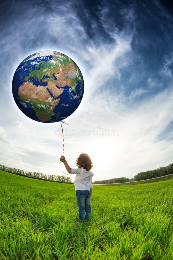Criança que guarda a terra nas mãos imagem de stock royalty free