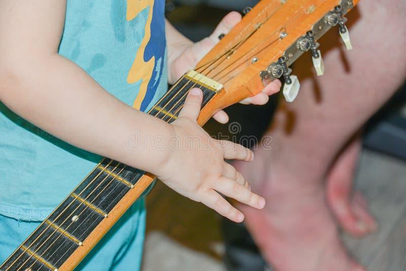 Criança que guarda uma guitarra fotos de stock royalty free