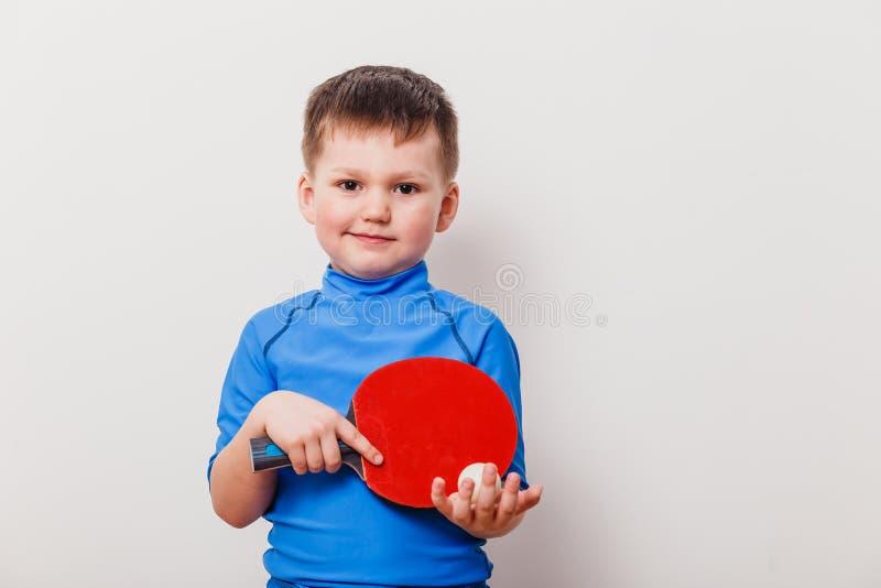 Criança que guarda uma raquete de tênis foto de stock