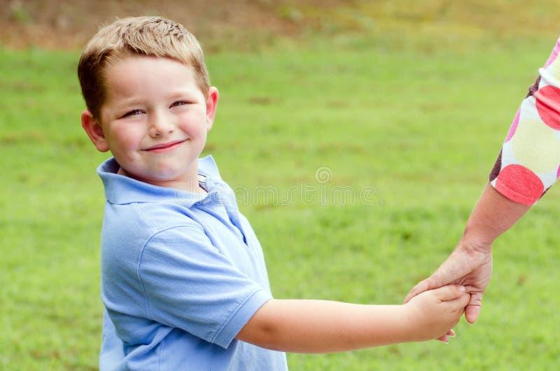 Criança que guardara as mãos com pai ao ir para a caminhada imagem de stock