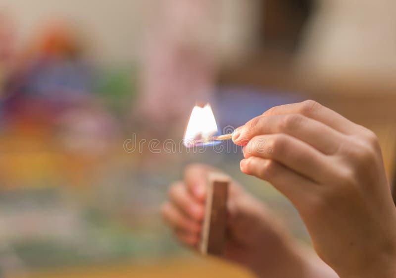 A criança que ilumina os fósforos O fogo nas mãos de uma criança fotografia de stock royalty free