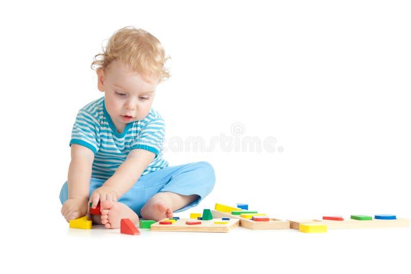 Criança que joga brinquedos lógicos da instrução com interesse fotografia de stock royalty free