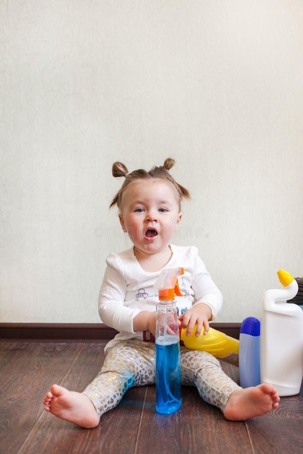 Criança que joga com as garrafas com os produtos químicos de agregado familiar que sentam-se no assoalho da casa foto de stock