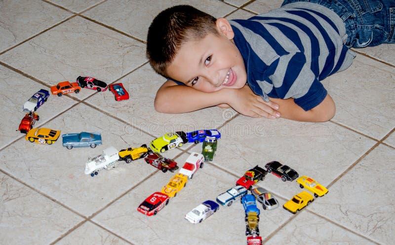 A criança que joga com carros do brinquedo soletra para fora o carro imagem de stock
