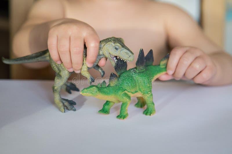 Criança que joga com duas figuras animais Os primeiros jogos de interpretação de personagem fotografia de stock royalty free
