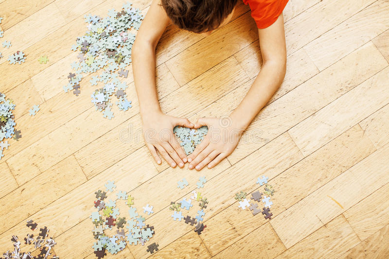 Criança que joga com enigmas no assoalho de madeira junto com o pai, conceito dos povos do estilo de vida, mãos loving a cada um fotografia de stock royalty free