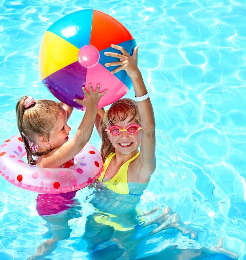 Criança que joga com a esfera na piscina. fotografia de stock