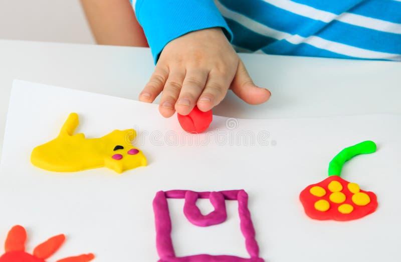 Criança que joga com formas do molde da argila imagem de stock
