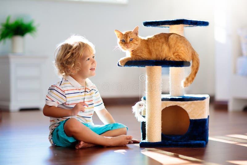 Criança que joga com gato em casa Crianças e animais de estimação imagens de stock