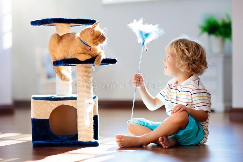 Criança que joga com gato em casa Crianças e animais de estimação fotografia de stock