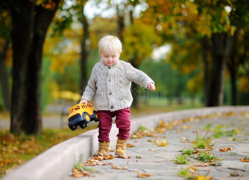 Criança que joga com o carro do brinquedo no parque do outono imagem de stock royalty free