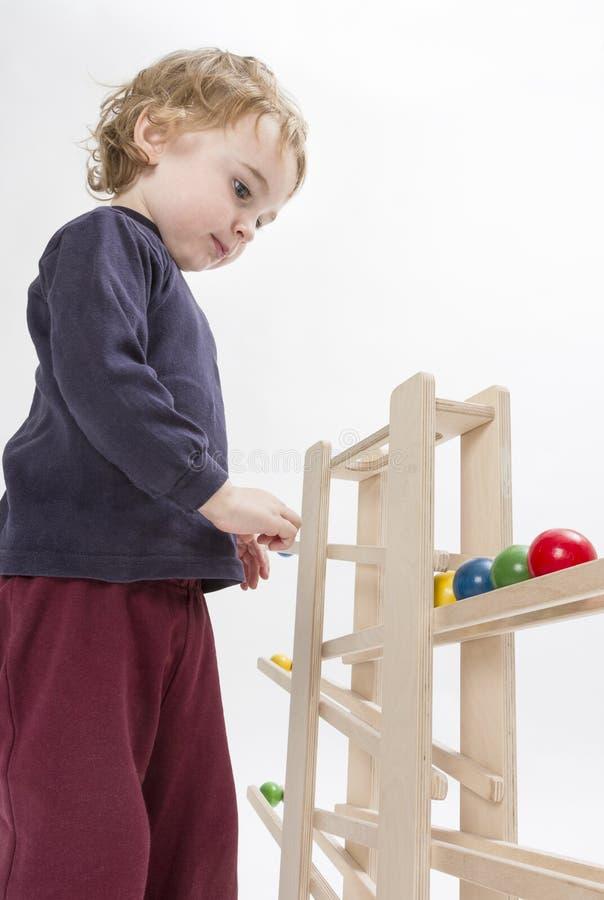Criança que joga com o trajeto de madeira da bola fotografia de stock