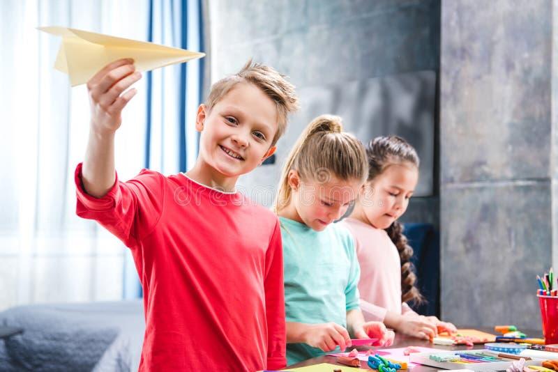 Criança que joga com os alunos planos de papel fotos de stock royalty free