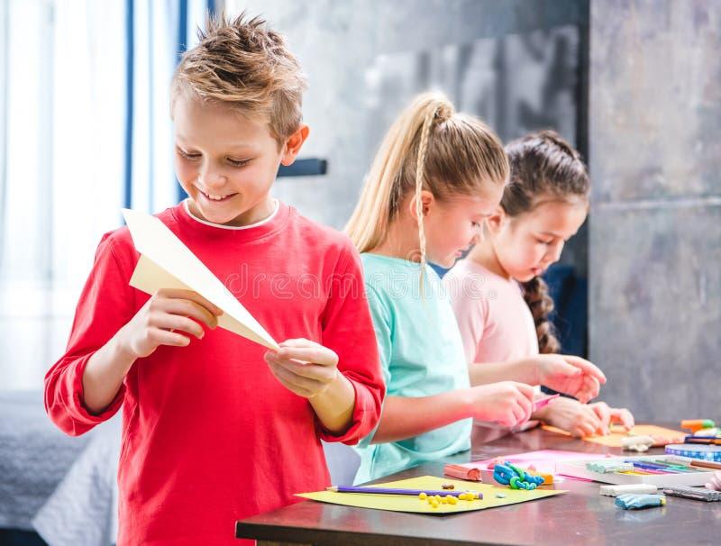 Criança que joga com os alunos planos de papel imagem de stock royalty free