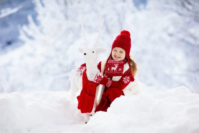 Criança que joga com a rena na neve em férias do Natal Divertimento exterior do inverno As crianças jogam no parque nevado na vés fotografia de stock