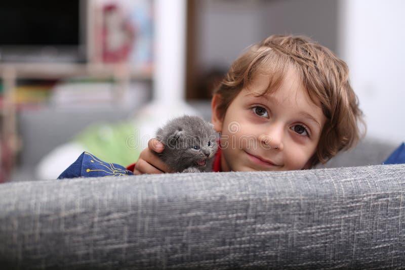 Criança que joga com um gatinho fotos de stock royalty free