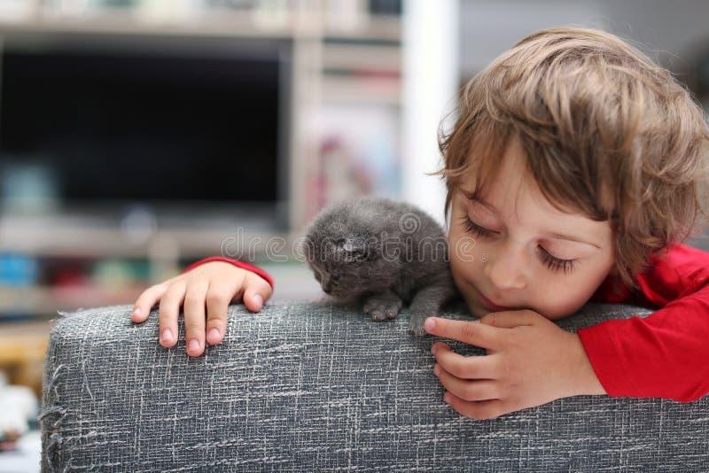 Criança que joga com um gatinho imagem de stock