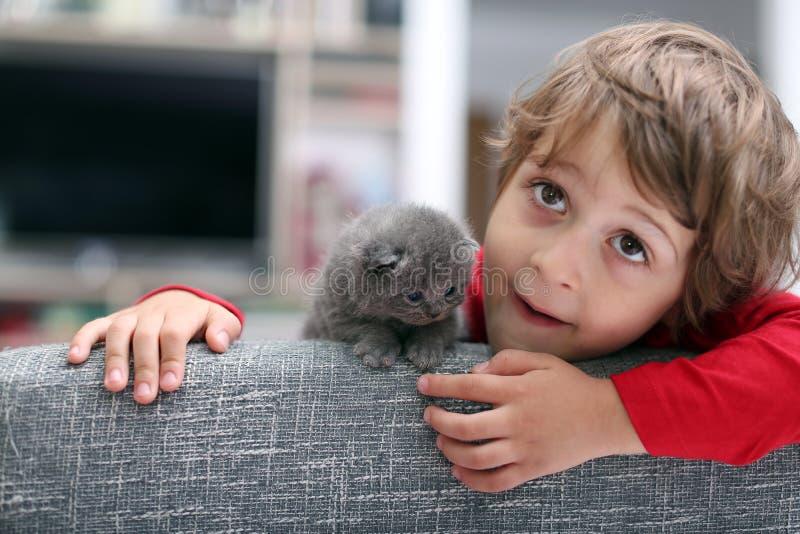 Criança que joga com um gatinho foto de stock
