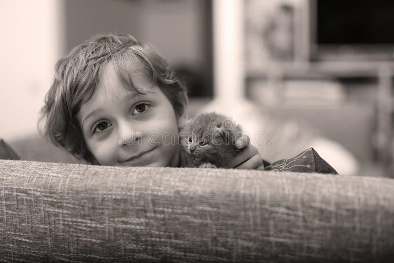 Criança que joga com um gatinho imagem de stock royalty free