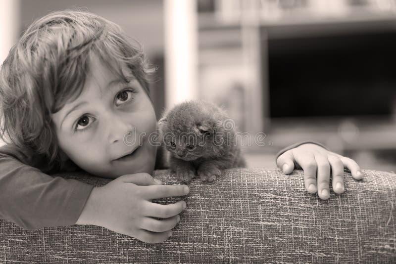 Criança que joga com um gatinho imagens de stock