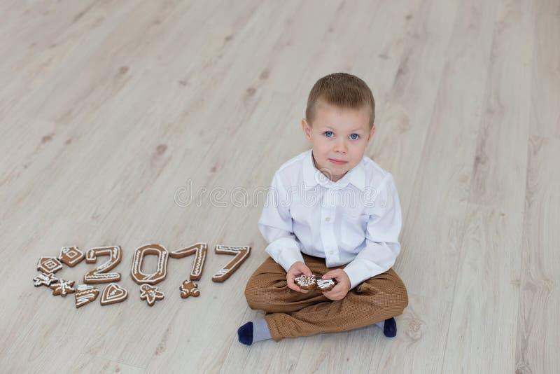 Criança que joga com véspera do ` s do ano novo do pão-de-espécie imagens de stock