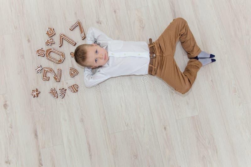 Criança que joga com véspera do ` s do ano novo do pão-de-espécie imagem de stock