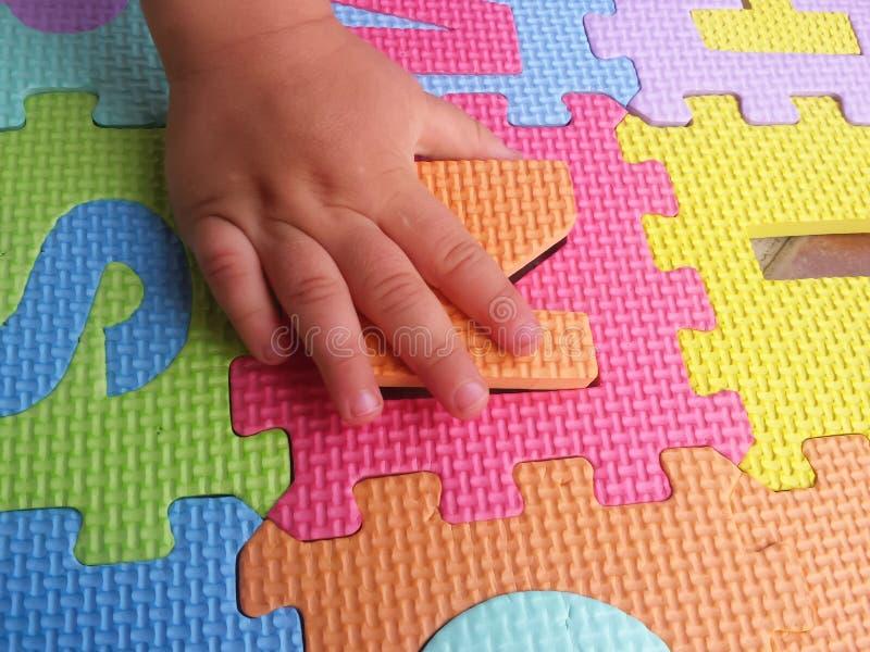 Criança que joga e que aprende letras com enigmas coloridos fotografia de stock royalty free