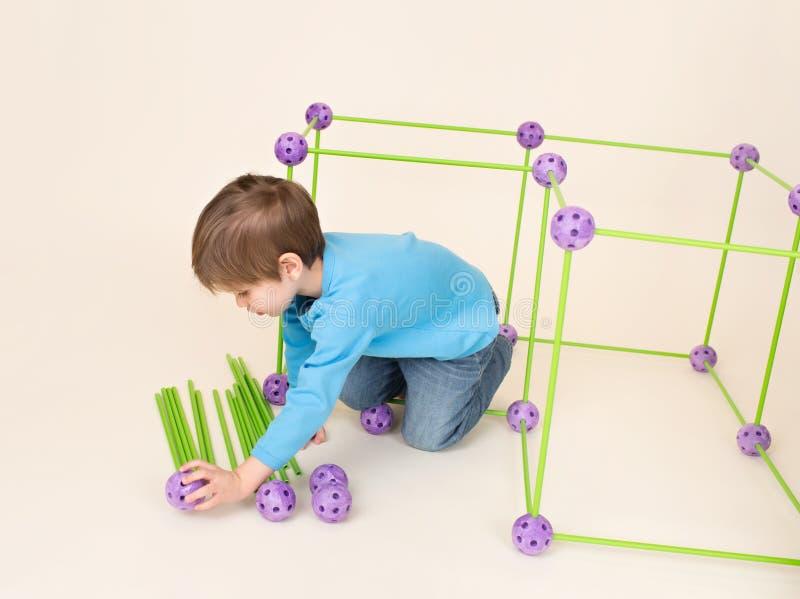 Criança que joga e que constrói um forte fotografia de stock