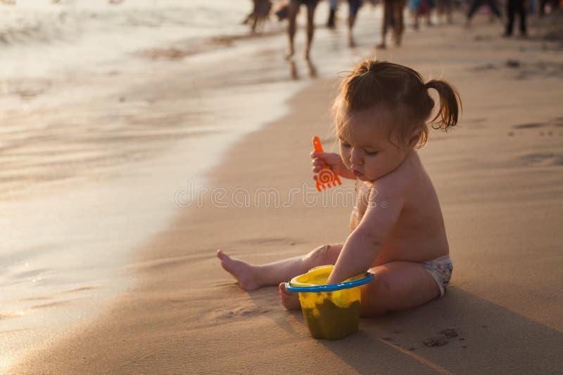 Criança que joga em um Sandy Beach, tempo do por do sol, ondas pequenas fotos de stock royalty free