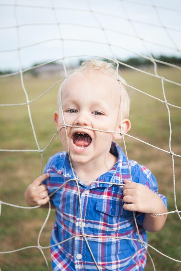 Criança que joga em uma rede do futebol fotografia de stock royalty free