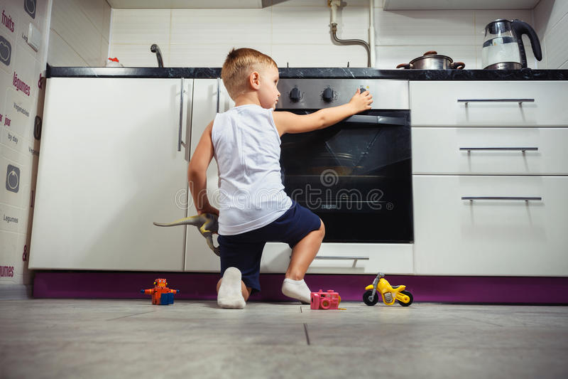 Criança que joga na cozinha com um fogão de gás imagem de stock