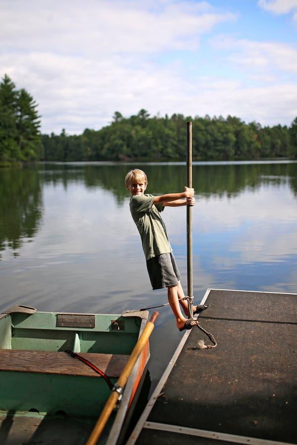 Criança que joga na doca pescando o barco de fileira no lago pequeno em madeiras do norte imagens de stock