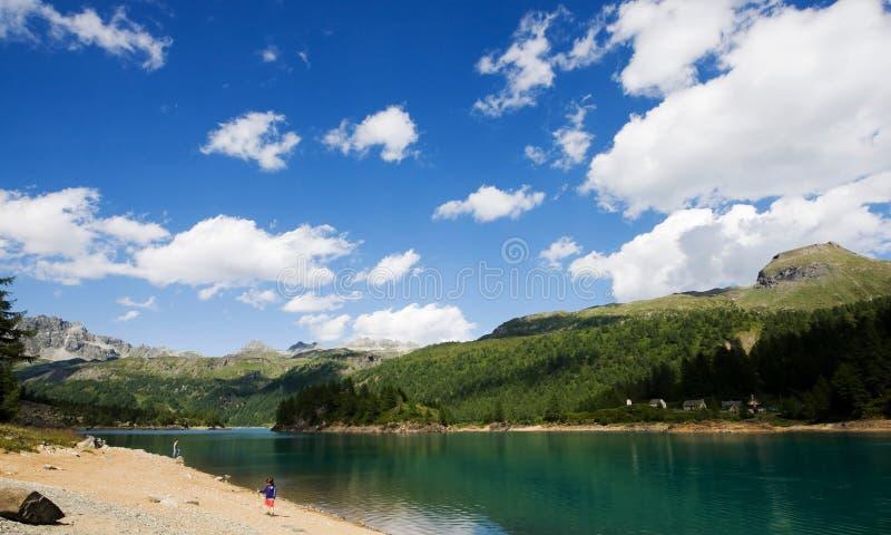 Criança que joga na frente do lago do devero imagens de stock