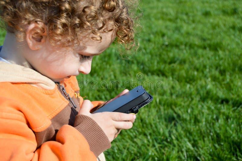 Criança que joga na grama imagens de stock